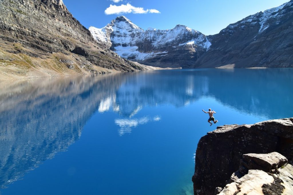 Alberta is the best province for road trips. Man jumping diving from cliff into mountain lake in the Rocky Mountains, Alberta Canada