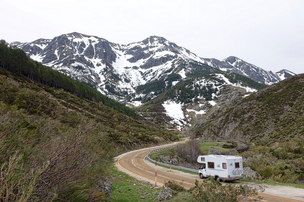 RV driving on mountain road toward snowy mountains. Motorhome rentals
