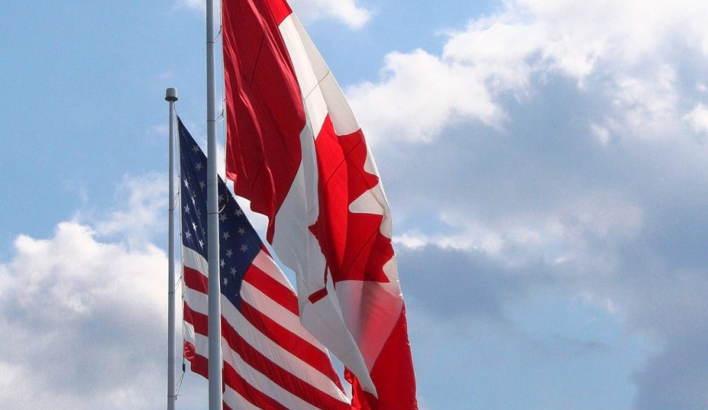 Candian and American flags, side by side. Border. Sky in background. import your RV or trailer into Canada