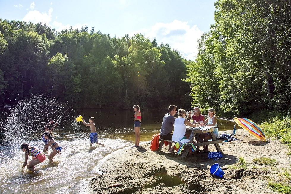 Family picnic by a lake. Canadian destinations for family summer vacations. Mactaquac Provincial Park, New Brunswick