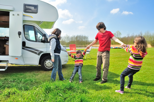 Family playing in front of RV, renting out your RV