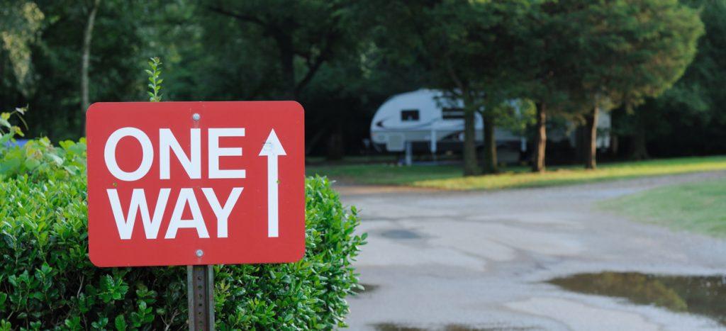 One way RV rentals - RV campground one way sign. RV in background