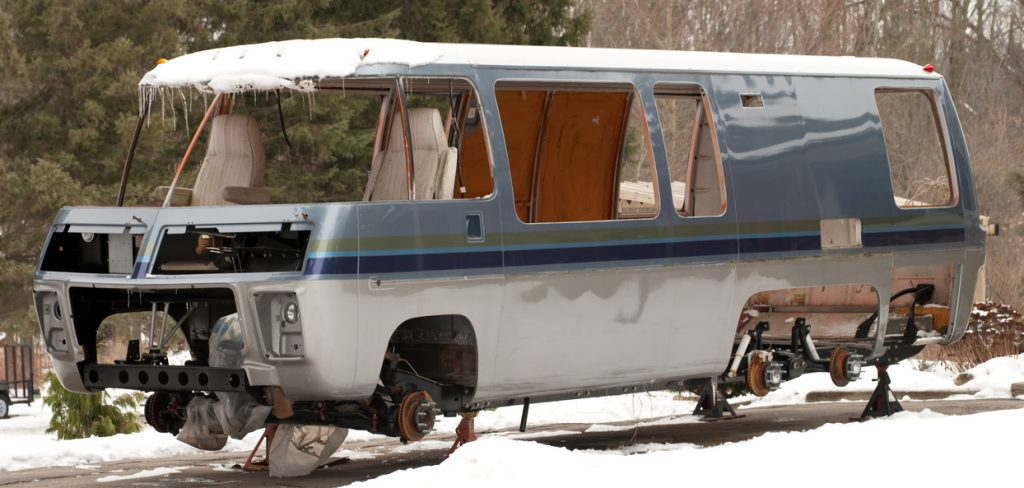RV tune-up checklist. A motor home being slowly repaired and rebuilt in the owners driveway, as seen on a winter day.