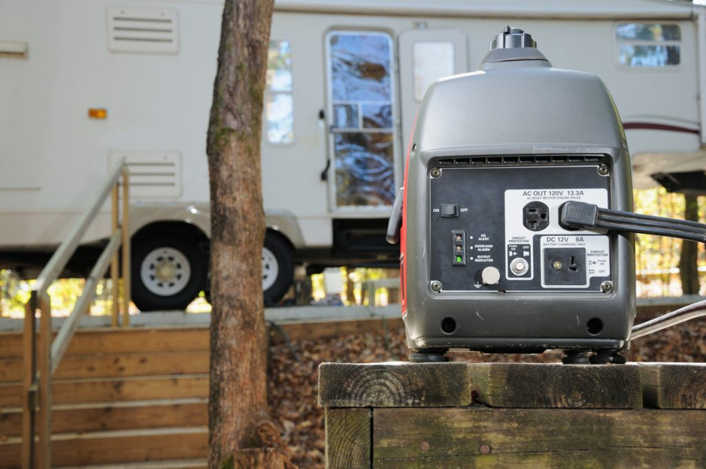 RV generator. Close up of portable gasoline generator providing power for fifth wheel RV trailer in campground