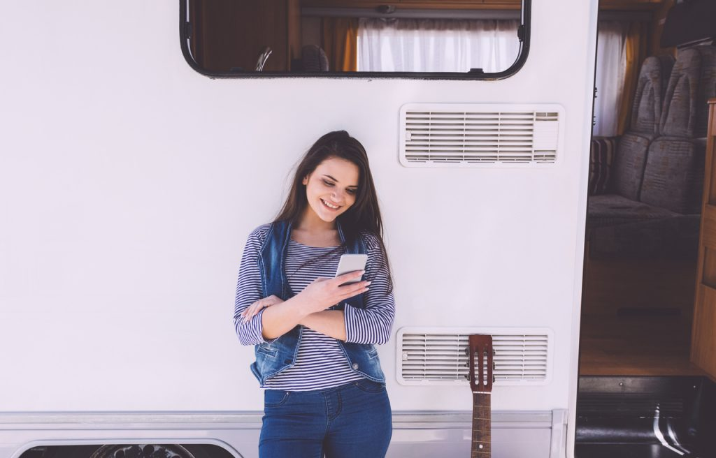 Grow your RV rental business with Facebook. Happy woman texting in front of the campervan