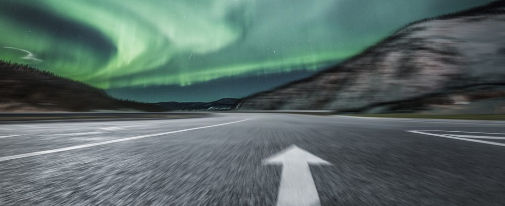 Uniquely Canadian. Aurora borealis over asphalt road in Yukon, Canada.