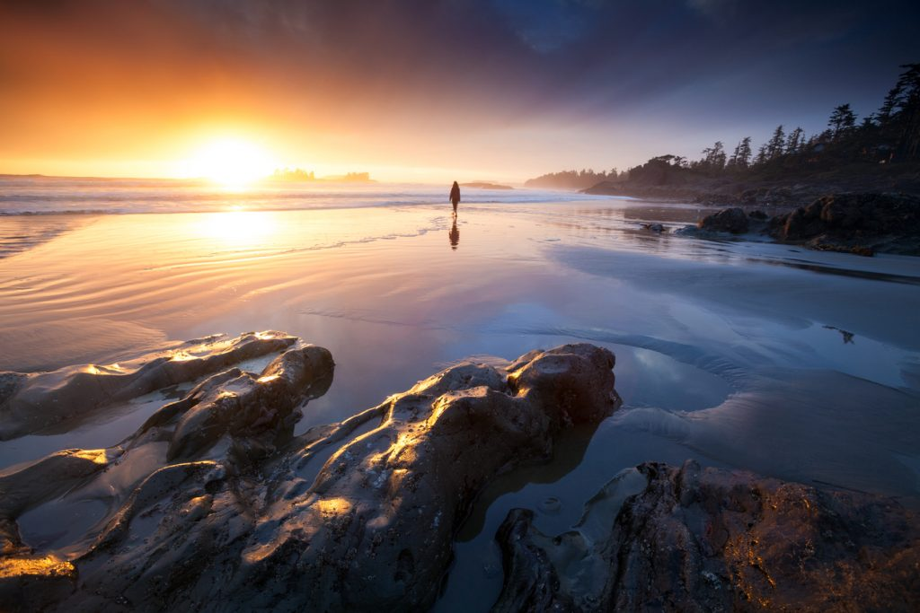 BC to Alberta RV trip. A silhouette of a young woman standing on a beach infront of a magnificant sunset, Tofino BC