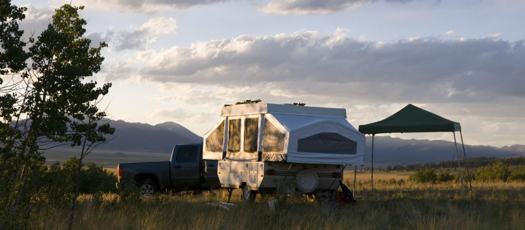 Small pop-up tent trailer camper sitting in an open meadow in the mountains.