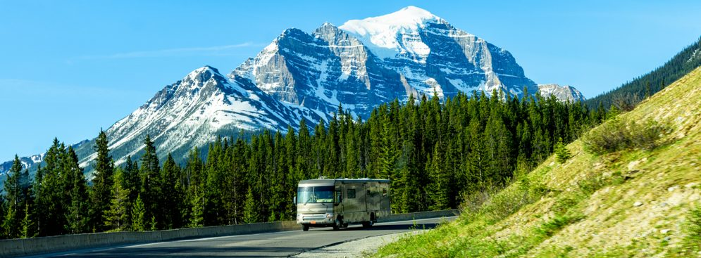 RVing in Canada. Luxury Class A motorhome drives on mountain road near Banff, Alberta, Canada